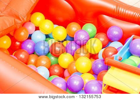 Holiday and children's party in a games room. A box filled with small colored balls. Children's colorful balls. A games room for child.