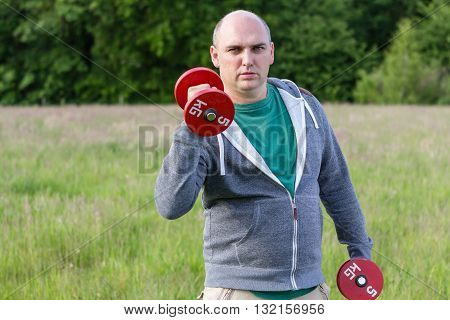 Man Working Outdoors With 5Kg Dumbbells Close Up
