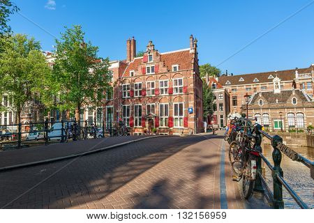 Bicycles on small bridge over canal and typical architecture on background in Amsterdam, Netherlands.
