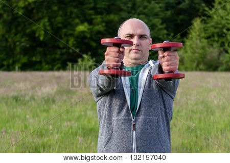 Sporty Man Holding Red Dumbbells With Arms Outstretched In Front Of Him