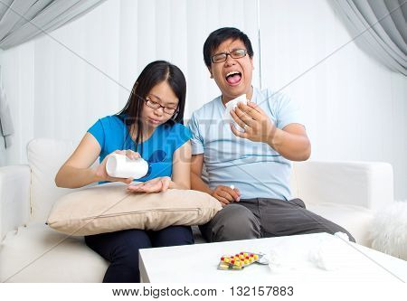 Asian man having medicine at home. Wife take care of her husband.