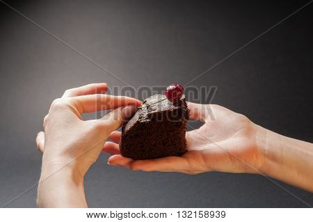 Slice of delicious chocolate cake with cherry on top in a woman hands on a dark background.