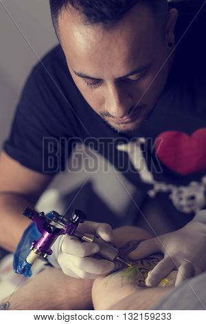Male tattoo artist holding a tattoo gun showing a process of making tattoos on a male tattooed model's arm.