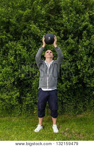 Man Is Exercising Outdoors With A 3 Kilogram Medicine Ball