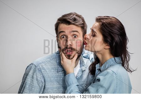 Portrait of happy couple kissing on gray background. Attractive man and woman being playful.