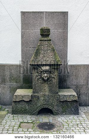 An old sculpture of medusa which may have been a drinking fountain at some time in the medieval city of Halmstad Sweden.