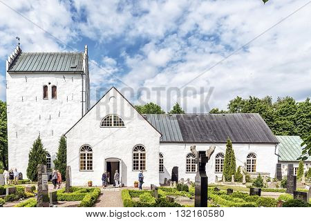 BILLESHOLM SWEDEN - MAY 28 2016.Parishioners leaving the old white norra vrams church in the swedish village of Billesholm.