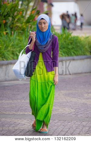 Kuching Sarawak Malaysia - August 10 2014: Portrait of woman wearing traditional Malay hijab and clothings while looking down in a crowded street of Kuching West sarawak Borneo Malaysia.