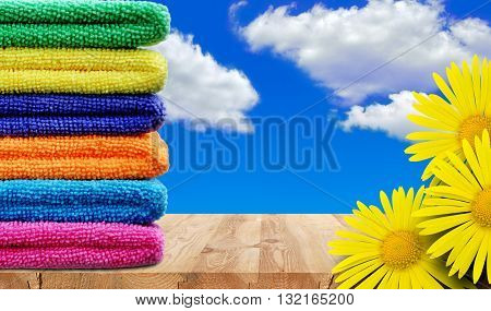 Stack of colored towels and yellow flowers on a wooden shelf against the sky
