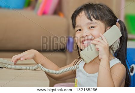 Little girl with phone calling holding telephone receiver at home
