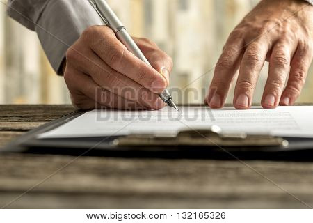 Front view of male hands signing document contract or application form on a clipboard with ink pen low angle view.