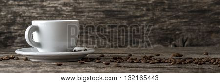 Panoramic view of white coffee cup on a plate on the left side of an image and scattered coffee beans on textured rustic wooden desk.