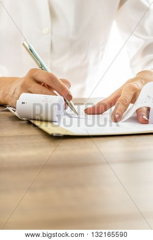 Closeup of female hands making calculations or annual financial report writing end sum on a printout receipt with calculator alongside on wooden desk.
