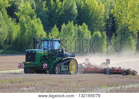 SALO, FINLAND - MAY 27, 2016: John Deere 9520T tracked tractor and cultivator on stubble field at spring in South of Finland.