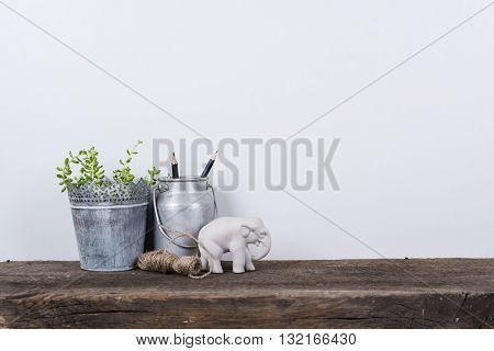 Scandinavian style home decor with plants on a rustic wooden board and white wall background.