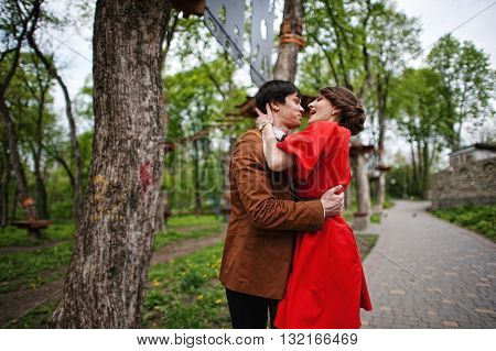 Happy Couple Passionate Kissing At Green Park. Stylish Man At Velvet Jacket And Girl In Red Dress In