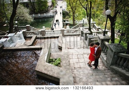 Couple Hugging In Love Background Stairs Of Park Bridge. Stylish Man At Velvet Jacket Hold Inf Hands