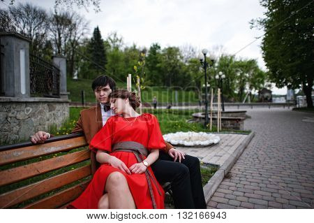 Couple Lying On The Bench. Stylish Man At Velvet Jacket And Girl In Red Dress In Love Together