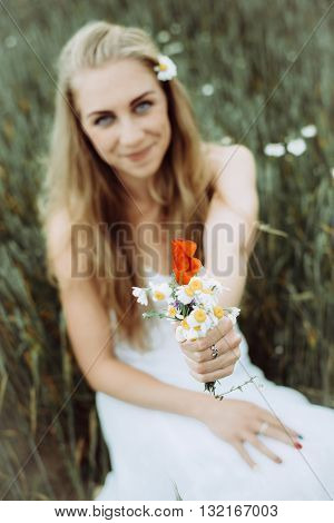 Beautiful girl with flower in the summer park.Blonde woman picking flowers.