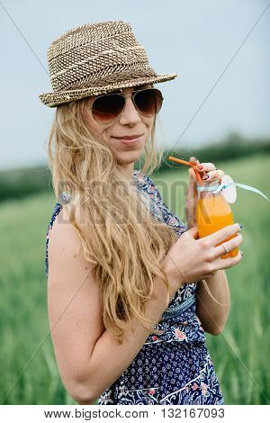 Woman drinking orange juice smiling and posing outdoor.