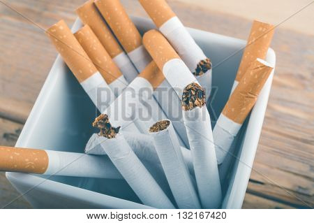 Quit Smoking - Broken Unsmoked Cigarettes In A White Ashtray With Blueish Filter