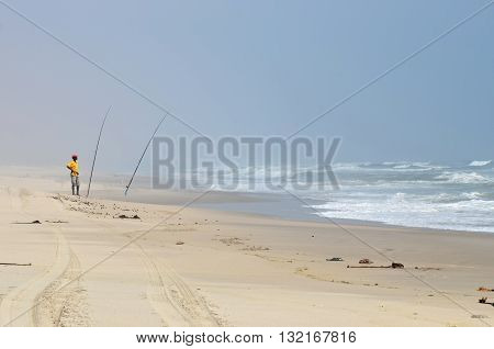 SKELETON COAST NAMIBIA - JAN 31 2016: Local fisherman on the Atlantic ocean shore where sand dunes meet the ocean. Fishing is popular between local people and tourists in Namibia