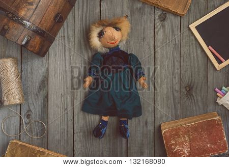 Vintage toy fantastic character elf lying on the wooden table with old books and a wooden chest top view