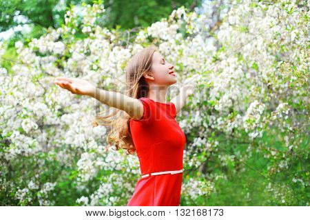 Beautiful Happy Young Woman Enjoying Smell In Flowering Spring Garden