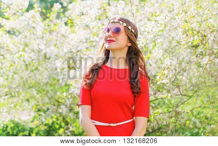 Beautiful Smiling Woman In Red Dress Looks With Hope Up Over Spring Flowering Garden
