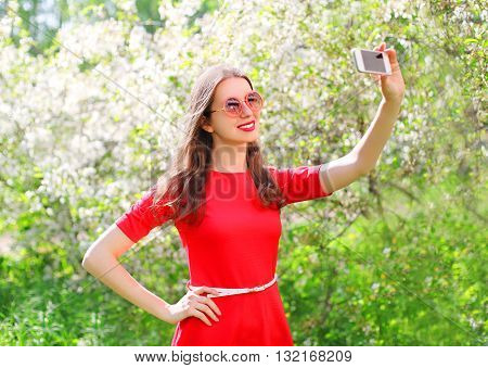 Beautiful Smiling Woman Makes Self Portrait On Smartphone In Spring Flowering Garden