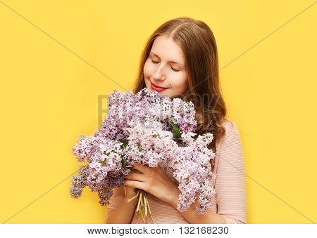 Cute Woman Enjoying Smell Of Bouquet Lilac Flowers Over Yellow Background