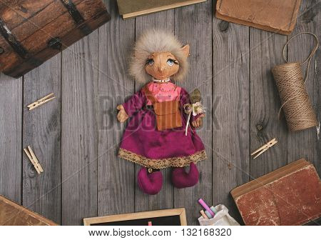 Vintage toy handmade fantastic character elf lying on the wooden table with old books and a wooden chest