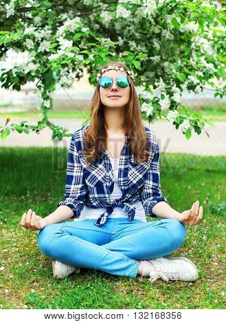 Fashion Hippie Woman Sitting Relaxes In Yoga Pose Lotus On Grass In Flowering Garden