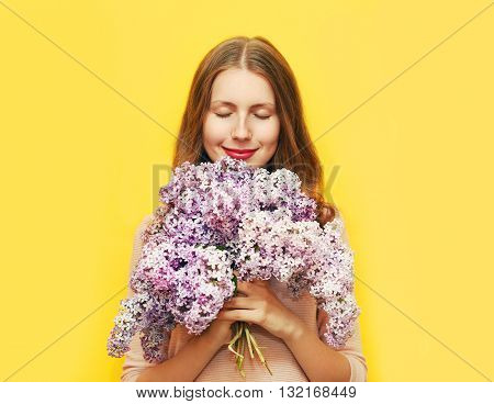 Happy Smiling Woman Enjoying Smell Of Bouquet Lilac Flowers Over Yellow Background