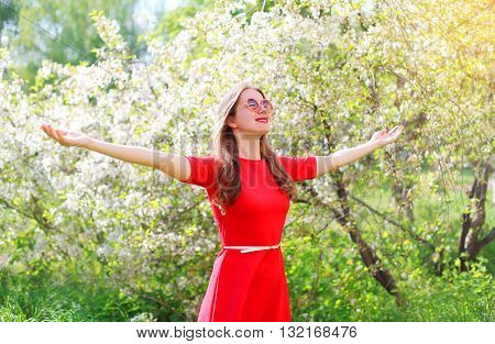 Happy Young Woman Enjoying Smell In Flowering Spring Garden