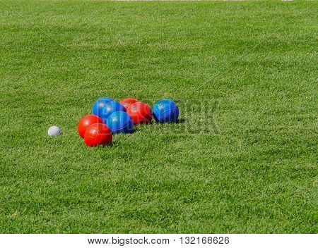 Red and blue boules or bowls on grass lawn