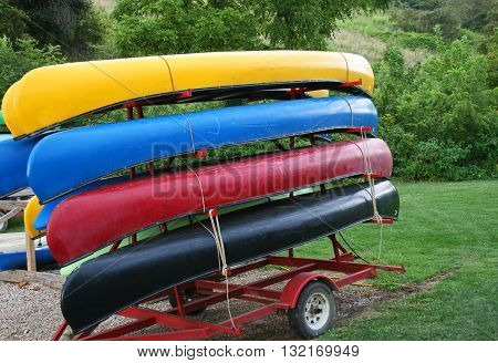Four colorful canoes on a canoe trailer