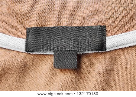 Blank black clothes label on beige cloth as a background
