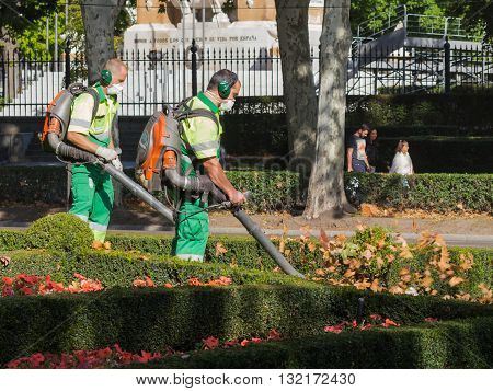 Madrid - 7 October 2015: Two men in a special protective clothing and masks blow away dust and leaves in a city park in the autumn of October 7 2015 Madrid Spain