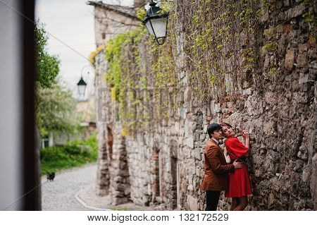 Couple Hugging In Love Background Stone Wall Of Castle. Stylish Man At Velvet Jacket And Girl In Red