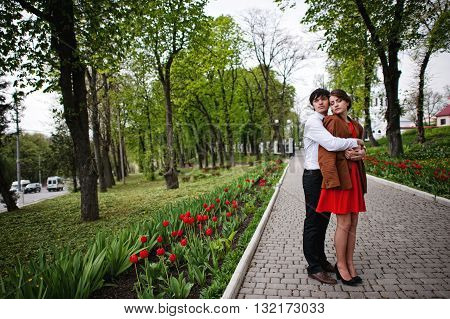 Couple Hugging In Love At Path With Tulip Flowers Garden. Stylish Man At Velvet Jacket And Girl In R
