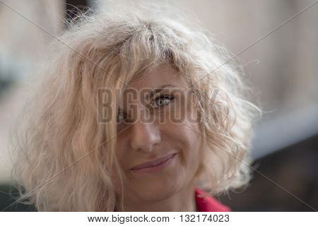 Portrait of beautiful curly blondie woman with stunning gray-blue eyes.