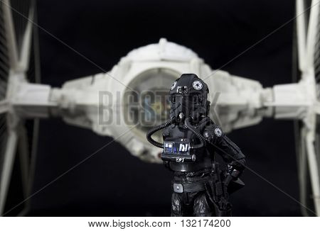 BLOOMFIELD NJ - MAY 30 2016: Hasbro Imperial Tie Fighter Pilot stands ready in front of a vintage Kenner Star Wars Tie Fighter.
