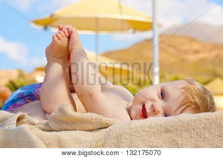 Smiling baby resting on the beach sunbed. Summer baby holidays