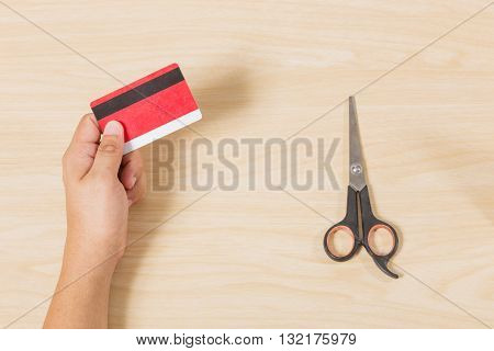Hand holding credit card and put scissors on wood table