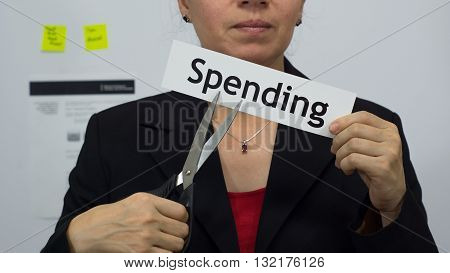 Female office worker or business woman cuts a piece of paper with the word spending on it as a spending reduction business concept.