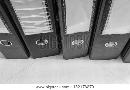 Closeup group of document file on wood desk background in black and white tone