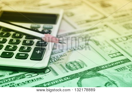 Pencil and calculator on dollar bank note money Finance concept