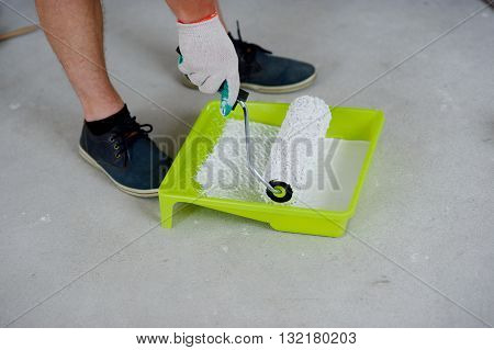 On a gray concrete floor there is a yellow tray. In him white paint. The hand in a working glove dips the roller into paint. Strong male legs in black footwear are also visible.