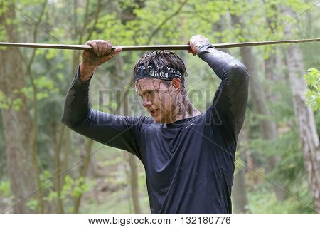 STOCKHOLM SWEDEN - MAY 14 2016: Concentrated man with mud in his face trying to maintain his balance on a slack rope in the obstacle race Tough Viking Event in Sweden April 14 2016